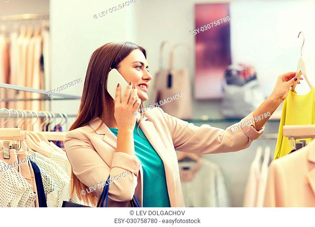 sale, consumerism, fashion, communication and people concept - happy young woman with shopping bags choosing clothes and calling on smartphone in mall or...