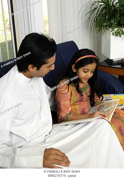 Father helping daughter with reading