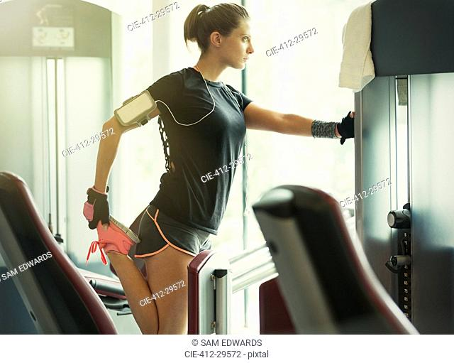 Focused woman stretching leg at exercise equipment in gym