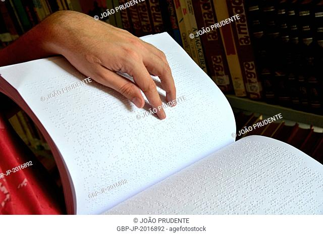 Visually impaired reading with your fingers book in braille in public city library - 10/2015