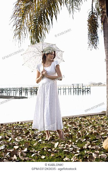 Portrait of elegant lady in white dress holding umbrella on water's edge at a garden party