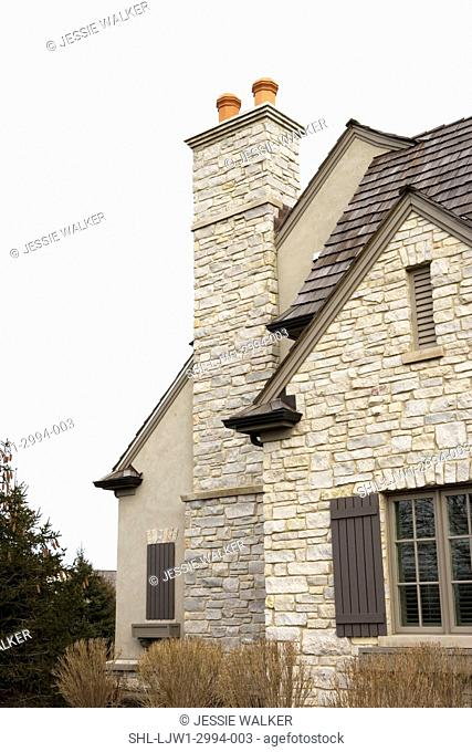 EXTERIORS: Close up architectural detail of outdoor chimney, French Normandy style home of stone and stucco with shutters, stone chimney and terra cotta flues