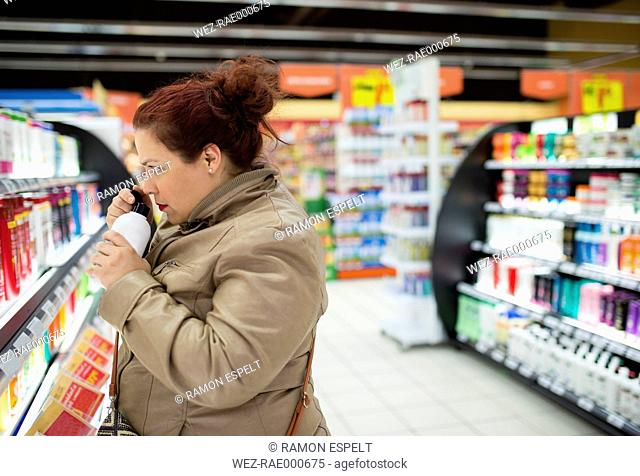 Woman in supermarket smelling at bath oil