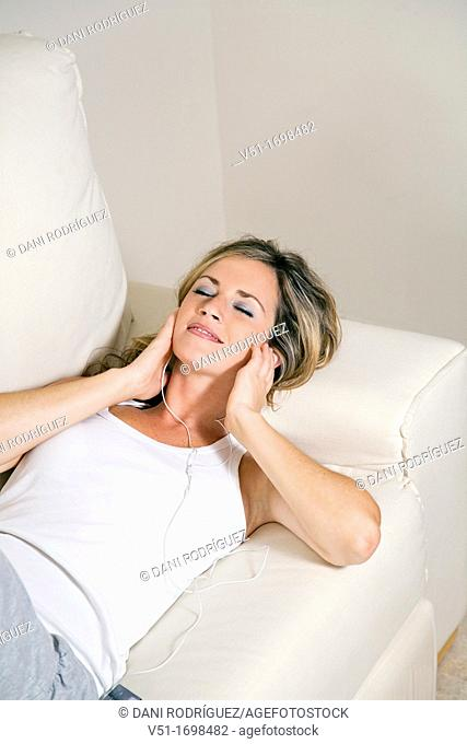 Woman, home, happy, leisure , smiling, couch, sofa, time out, music, listening