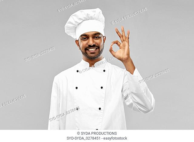 happy male indian chef in toque showing ok gesture