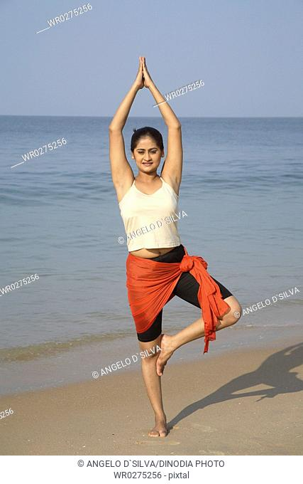 South Asian Indian young lady doing aerobics in welcome posture on seashore , Shiroda , Dist Sindhudurga , Maharashtra , India MR703E