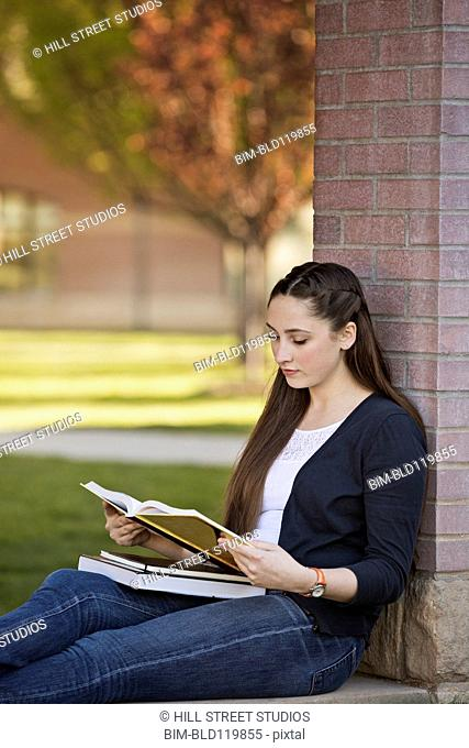 Caucasian student reading on campus
