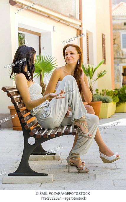 Two young women talk on wooden bench