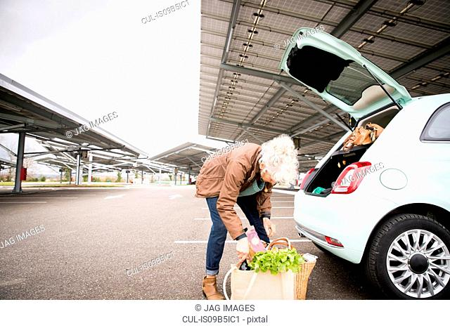 Mature woman in car park, loading shopping into boot of car