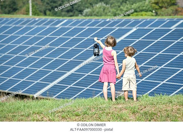 Children standing together in front of solar panels, girl holding old-fashioned latern