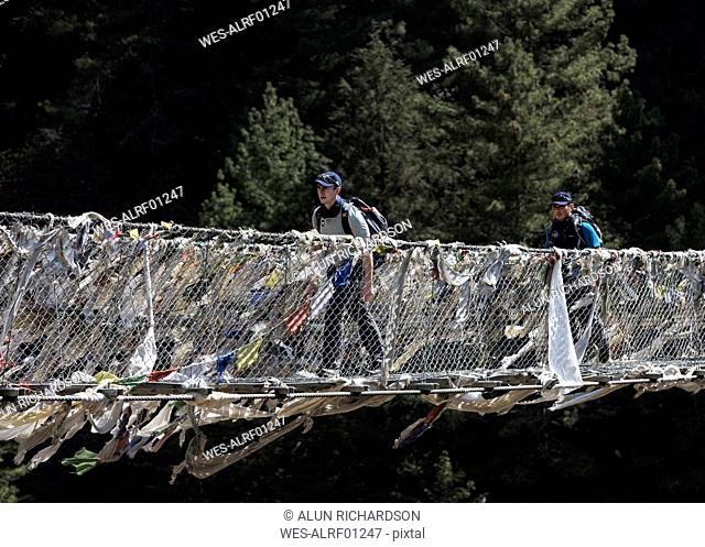 Nepal, Solo Khumbu, Everest, Sagamartha National Park, Two people crossing suspension bridge