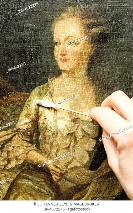 Restoration studio, restorer, hand cleans a painting with cotton swabs, Munich, Bavaria, Germany