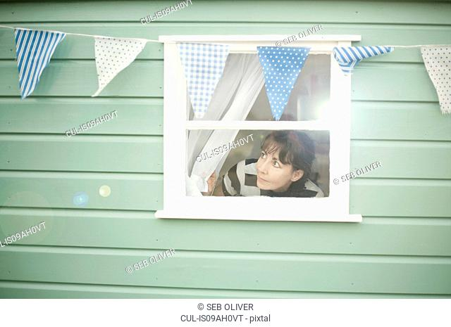 Mature woman peering out of beach hut window