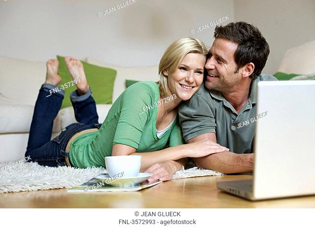 Couple lying on floor and looking at laptop
