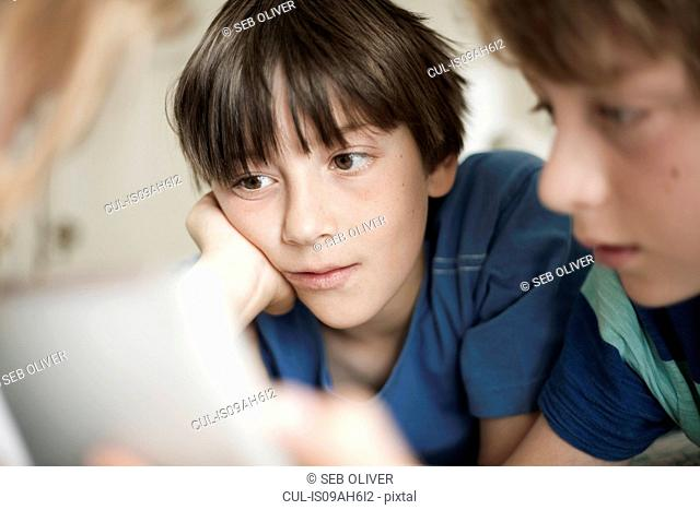 Close up of two brothers engrossed by digital tablet