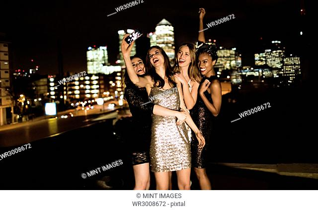 Group of young women standing on a rooftop posing for a photograph