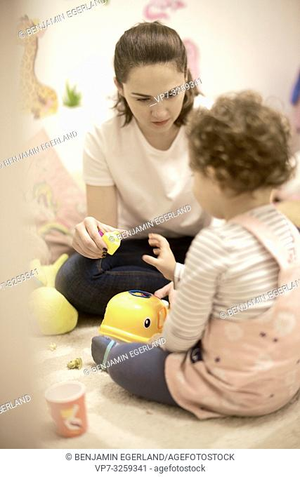 woman playing with toddler at home in child's room, in Munich, Germany