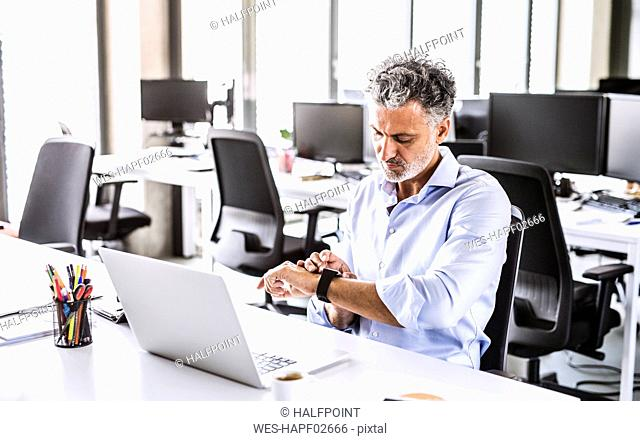 Mature businessman sitting at desk in office looking at smartwatch