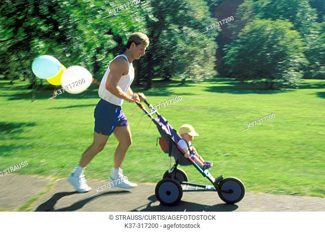 Jogger father with baby son sitting in stroller