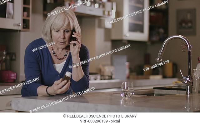 MODEL RELEASED. Senior Adult woman calling doctor and holding medicine at home