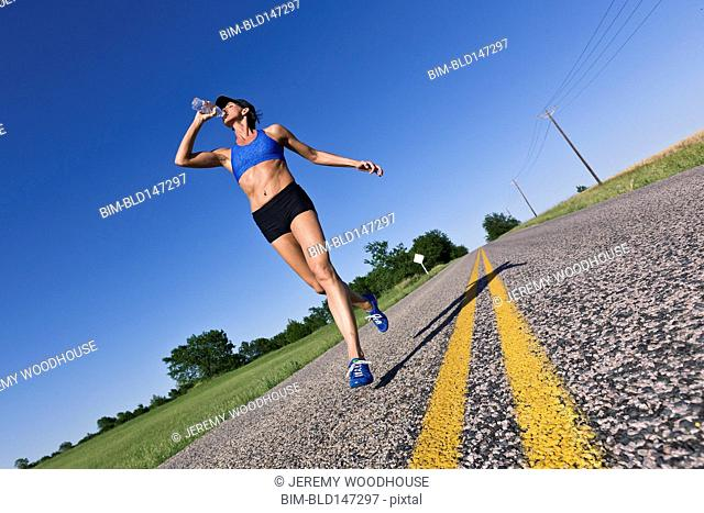 Caucasian runner training on remote road and drinking water