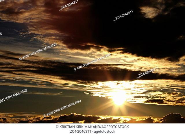 Dramatic sunrise in cloudy sky. Scandinavia