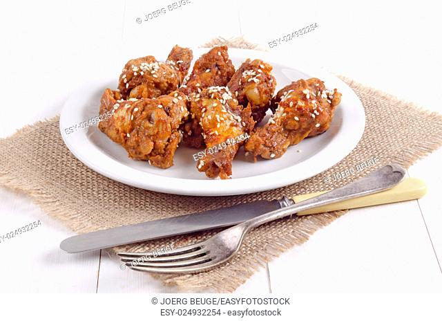 grilled chicken drumsticks with sesame seeds on a white plate