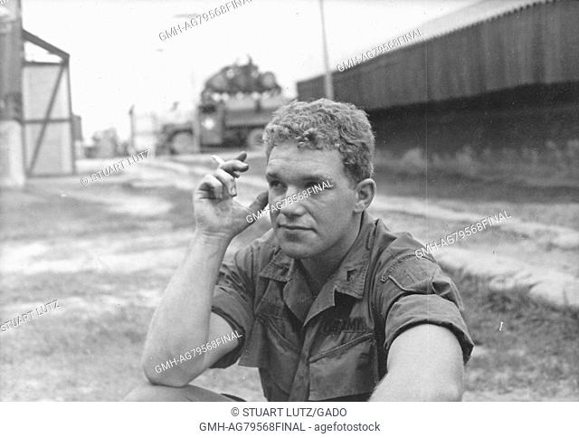 A United States Army serviceman sitting on the ground and smoking a cigarette, buildings and utility poles can be seen on the base behind him, Vietnam, 1967