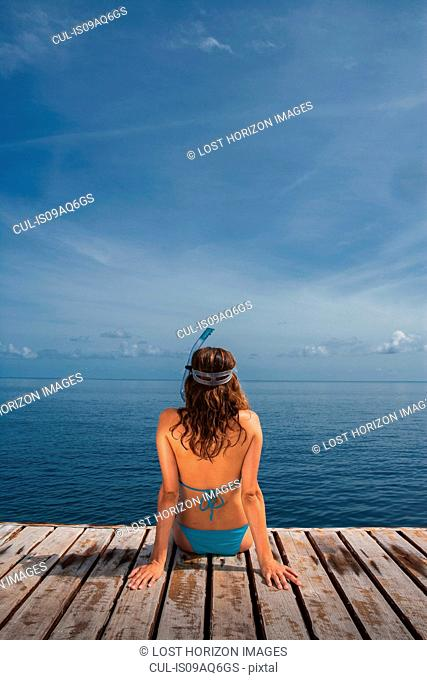 Mid adult woman sitting on pier looking at sea