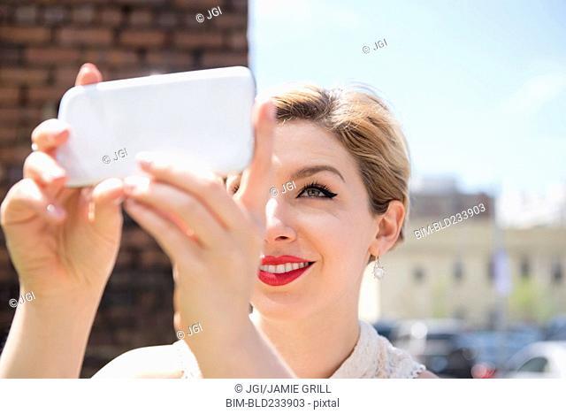 Caucasian woman posing for cell phone selfie