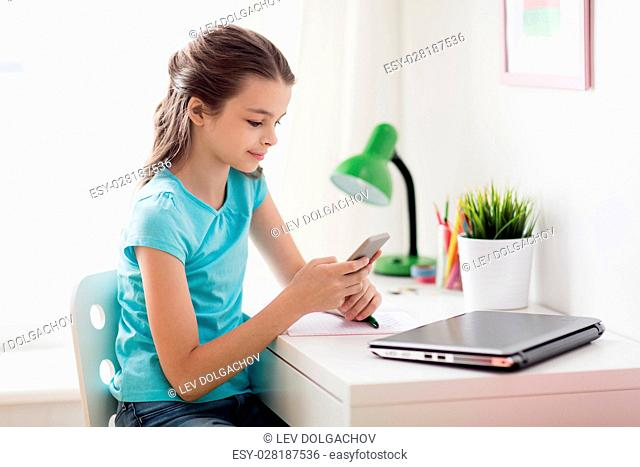 people, children and technology concept - girl with laptop computer and smartphone texting at home