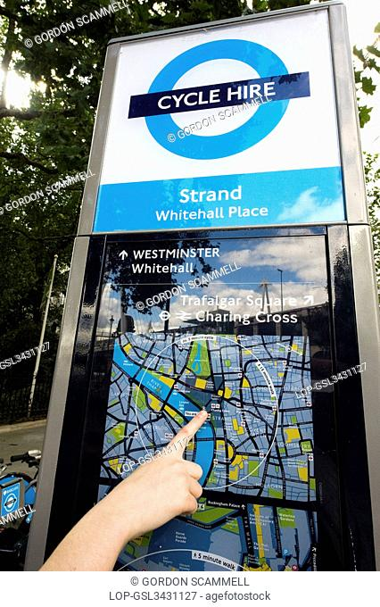 England, London, Westminster. Close-up of a persons hand pointing out their location on a map at a terminal of a Barclays Cycle Hire docking station