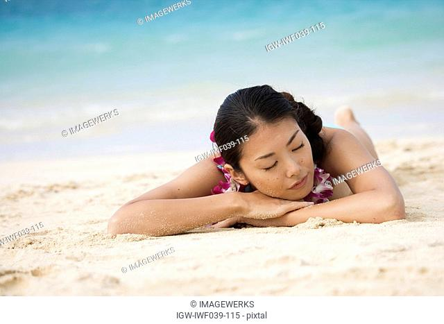A young woman sleeping on sand at beach