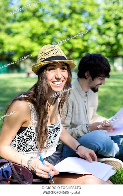 Portrait of happy young student sitting in the park