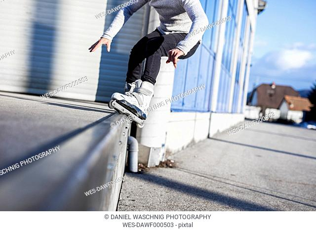 Low section of young man doing a trick on inline skates