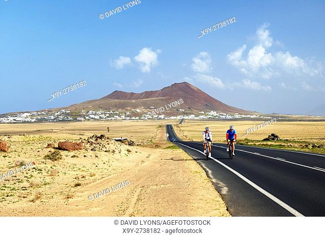 Cycling on the LZ-401 road from volcanic cone rising above village of Soo. Teguise, Lanzarote, Canary Islands, Spain