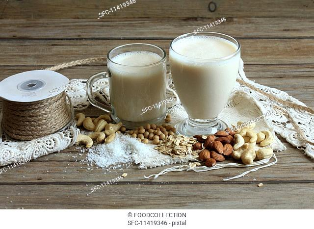 Two glasses of vegan milk, nuts, soya beans and oats