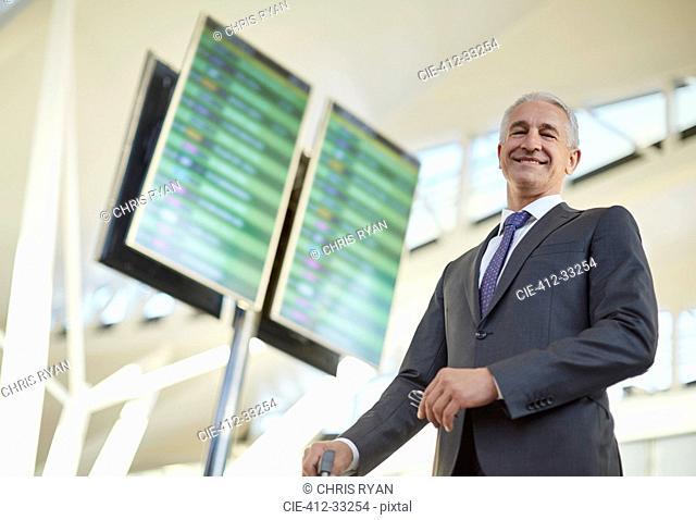 Portrait smiling businessman standing below arrival departure board in airport