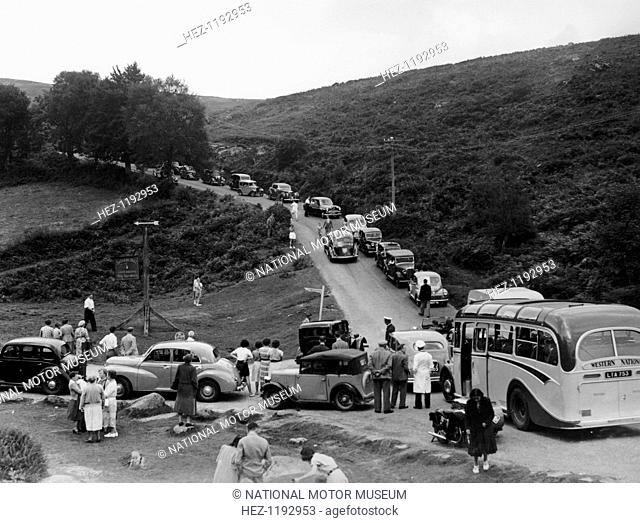 Crowded road at Dartmeet, Devon, c1951. People are milling around stationary cars and a coach caught up in a traffic jam at the junction of two country roads in...