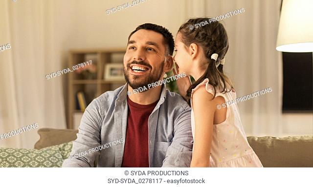happy daughter whispering secret to father at home