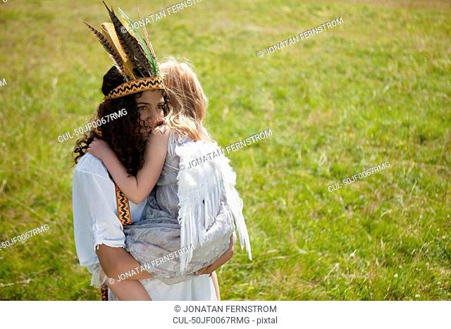 Girls in costume hugging outdoors