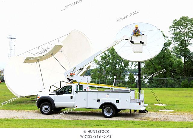 Communications engineer in bucket truck in front of satellite dish
