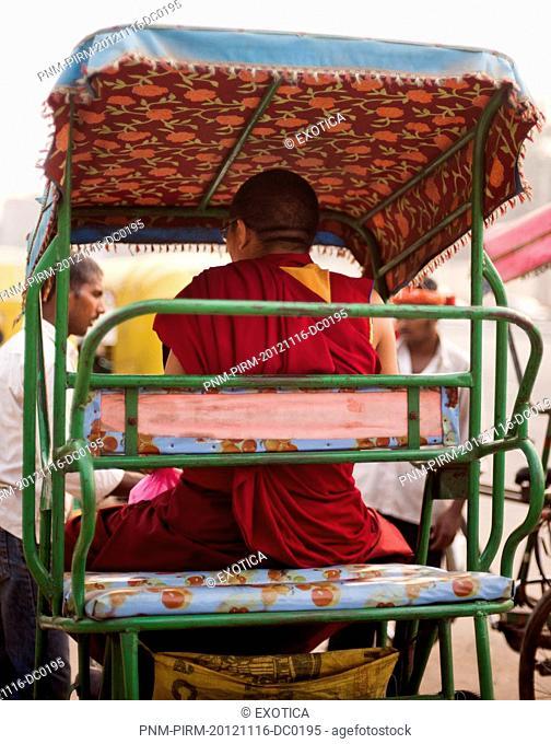 Monk sitting on a rickshaw, Tibetan Monastery, Delhi, India