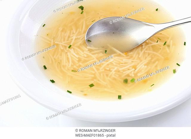 Noodle soup on plate with spoon, close-up