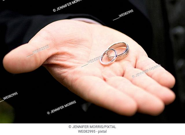 Two white gold wedding rings rest in the open hand of the groom against the black background of his tuxedo
