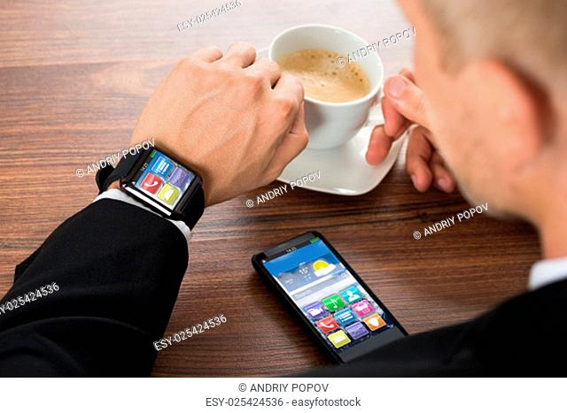 Close-up Of Businessman With Smartphone And Smartwatch Holding Cup Of Coffee On Desk