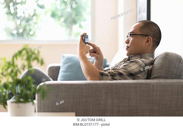 Korean man using cell phone on sofa
