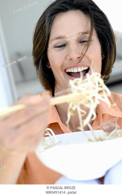 Close-up of a mature woman holding a bowl of bean sprouts