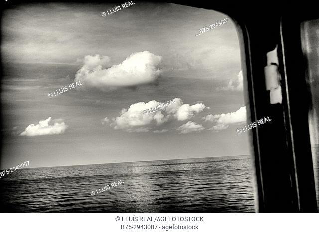 View of sea and clouds through ship window. Mediterranean Sea, Balearic Islands, Spain