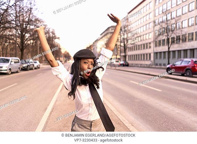happy stylish woman jumping in evening sunlight at street, wearing retro business outfit, individual look, African Angolan descent, in city Munich, Germany